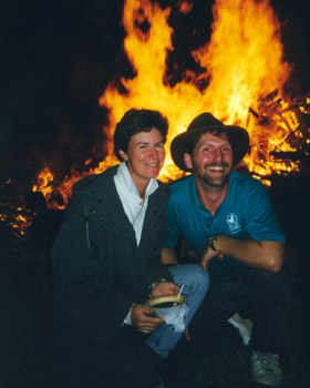 juli and larry posing in front of a bonfire